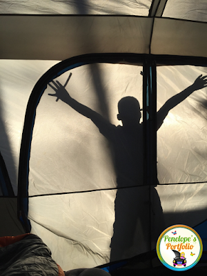 A boy having fun standing outside of a tent at night, while his shadow is visable