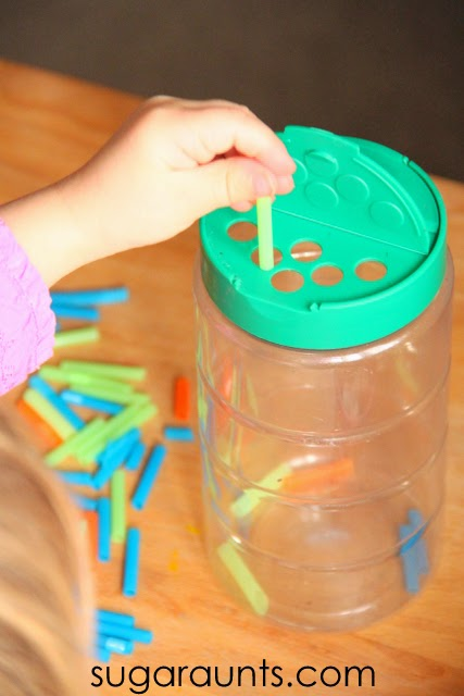 Toddlers and preschoolers can work on their tripod grasp by using small pieces of straws and a recycled grated cheese container.