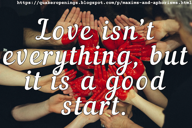 """Photograph shows lots of people holding their hands flat, palms towards the camera, alongside one another, to form a nearly solid area of palms. On this area is drawn a heart in glossy red pigment. Text overlay reads """"Love isn't everything, but it is a good start."""""""