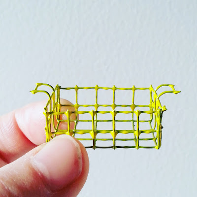 Hand holding up a one-twelfth scale modern miniature wire basket with handles, painted yellow.
