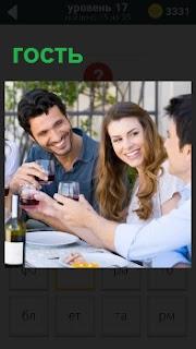 Девушка с парнем принимают гостя за столом и в руках бокалы с красным вином