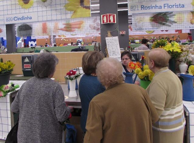 várias senhoras a conversar com uma florista do Mercado Temporário do Bolhão