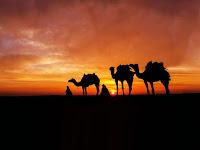 Gün batımında develer ile çölde yolculuk, hicret tasviri