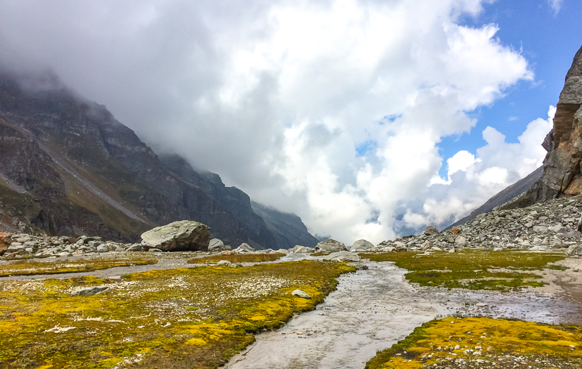 """Hampta Pass – A crossover trek from kullu to spiti valleyIt had been two months since my last visit to the mountains and something was kicking inside. A three days long weekend was approaching, and one of the friends in the group suggested idea to trek to hampta pass.A few details about the trek: Hampta pass is a special pass that takes you from lush green mountains of kullu valley to barrens of lahaul valley on other side. It lies at an altitude of 14000 ft. (approx). Local shepherds use this high altitude pass to take their herds for grazing in Lahaul Spiti where special grass known as """"Neeru"""" grows considered a very good source of nutrients for sheep and goatsSo, three of us were coming from Noida, and plan was to meet at manali. Starting our journey at evening of 9th September, we reached manali in the morning. As I was coming from Hamirpur, approx. 200 kms from Manali, I had reached earlier. We all met each other and exchanged pleasantries and soon we were ready for all the thrill and adventure that was waiting for us in the mountains. We asked around and collected some information about the trek, things we need, food etc. and then hired a taxi from manali to jobra. It took around one and half hour to reach Jobra. The road is in bad condition with countless hairpin bends. In Jobra, there is only one small shop around for snacks etc. We had tea and lunch in Jobra. Then we met a group of people who were also going for trek. However, they had tents, food and other things with them. They told us that there are no tents available in the journey and we shall aim to reach """"Balu ka Dera"""", where we can find accommodation. So, we started trekking around 03:00 PM from Jobra with a small trail through pine forests and leading to lush green meadows with small rocks. Rani river/nala flows in between or either sides of the meadows. We reached Chilka, which is roughly 4 kms from Jobra and saw a campsite there. It was YHAI campsite and there were around 25 to 30 people there. T"""