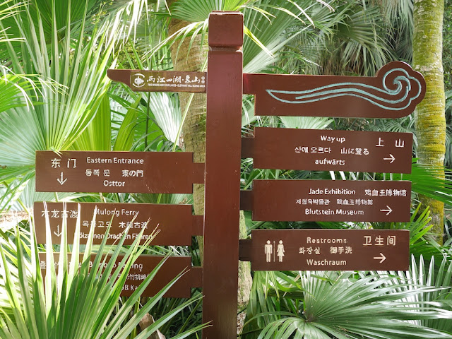 directional signs with locations written in five languages
