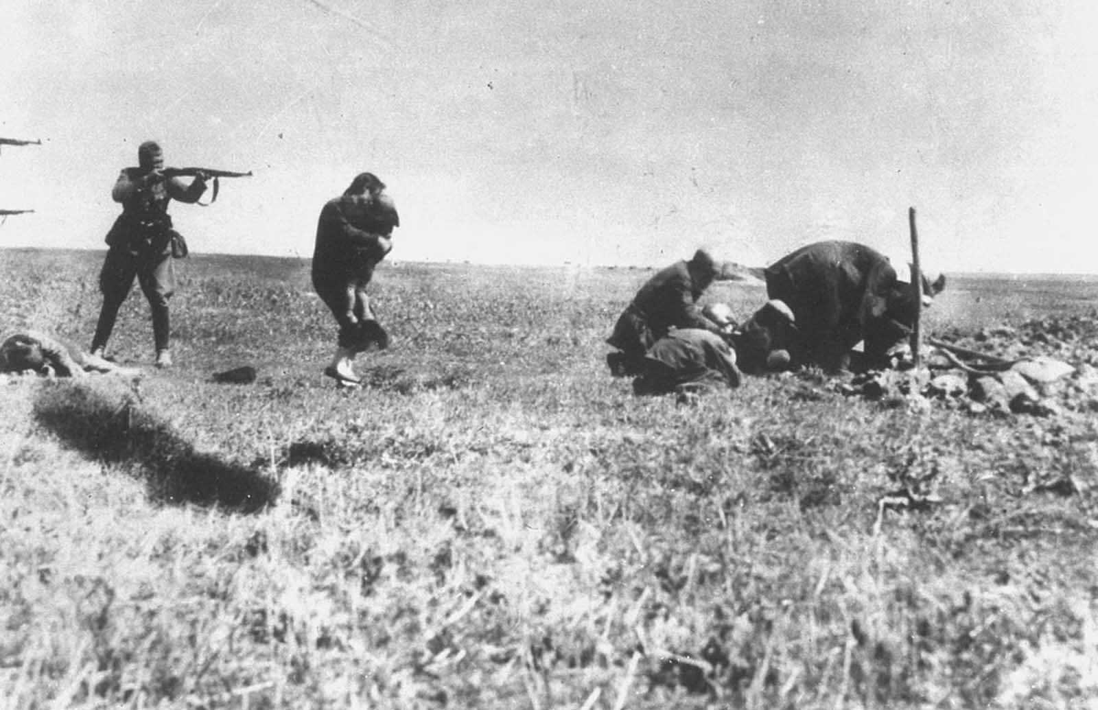 An execution of Jews in Kiev, carried out by German soldiers near Ivangorod, Ukraine, sometime in 1942. This photo was mailed from the Eastern Front to Germany and intercepted at a Warsaw post office by a member of the Polish resistance collecting documentation on Nazi war crimes. The original print was owned by Tadeusz Mazur and Jerzy Tomaszewski and now resides in Historical Archives in Warsaw. The original German inscription on the back of the photograph reads,