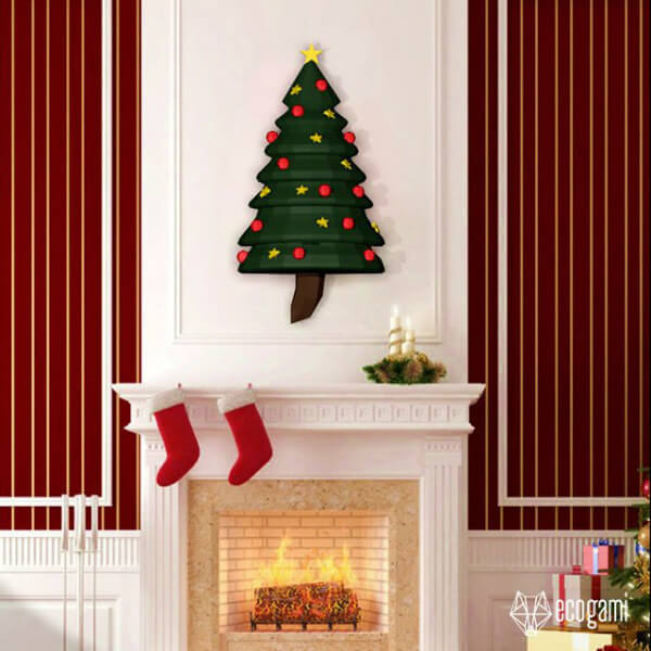 dimensional paper craft Christmas tree hanging above a fireplace mantel