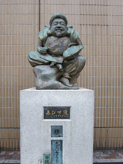 Ebisu, statue outside the Ebisu train station in Tokyo. A bronze statue of a small seated man, smiling and holding a fish, in front of a tiled wall.