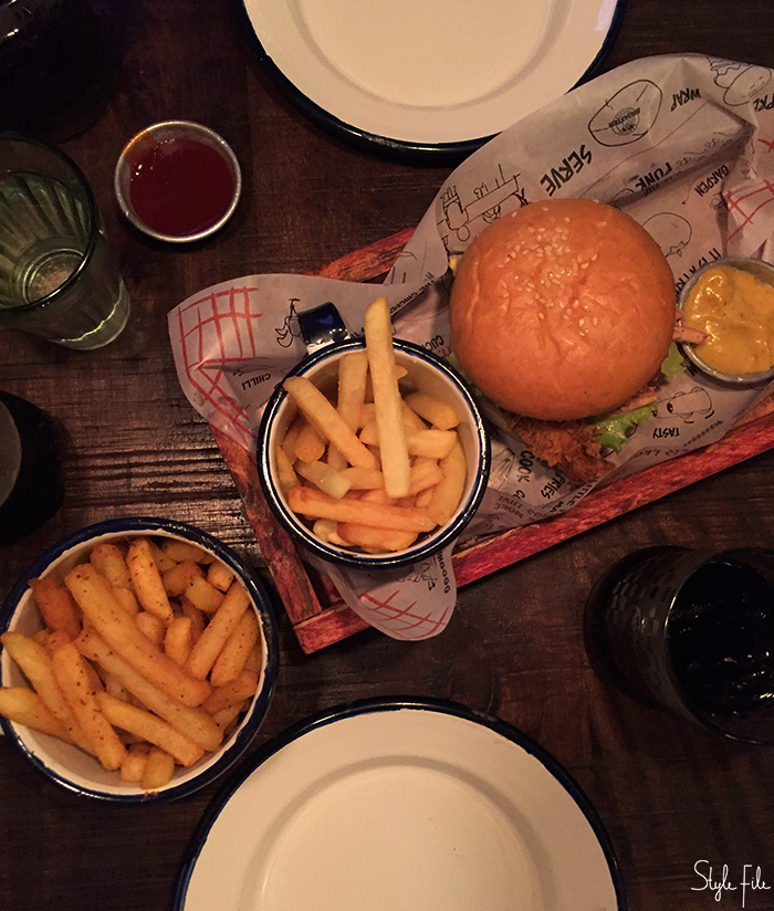 Flat lay image of a chicken burger along with potato french fries and a glass of coke on a wooden table