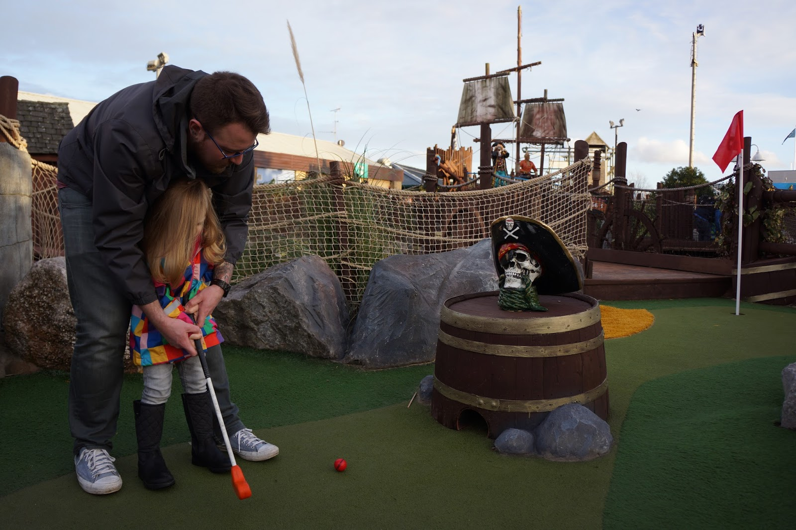 dad and daughter playing mini golf