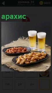 На столе стоят два бокала с пивом и в тарелках в качестве закуски орешки арахис