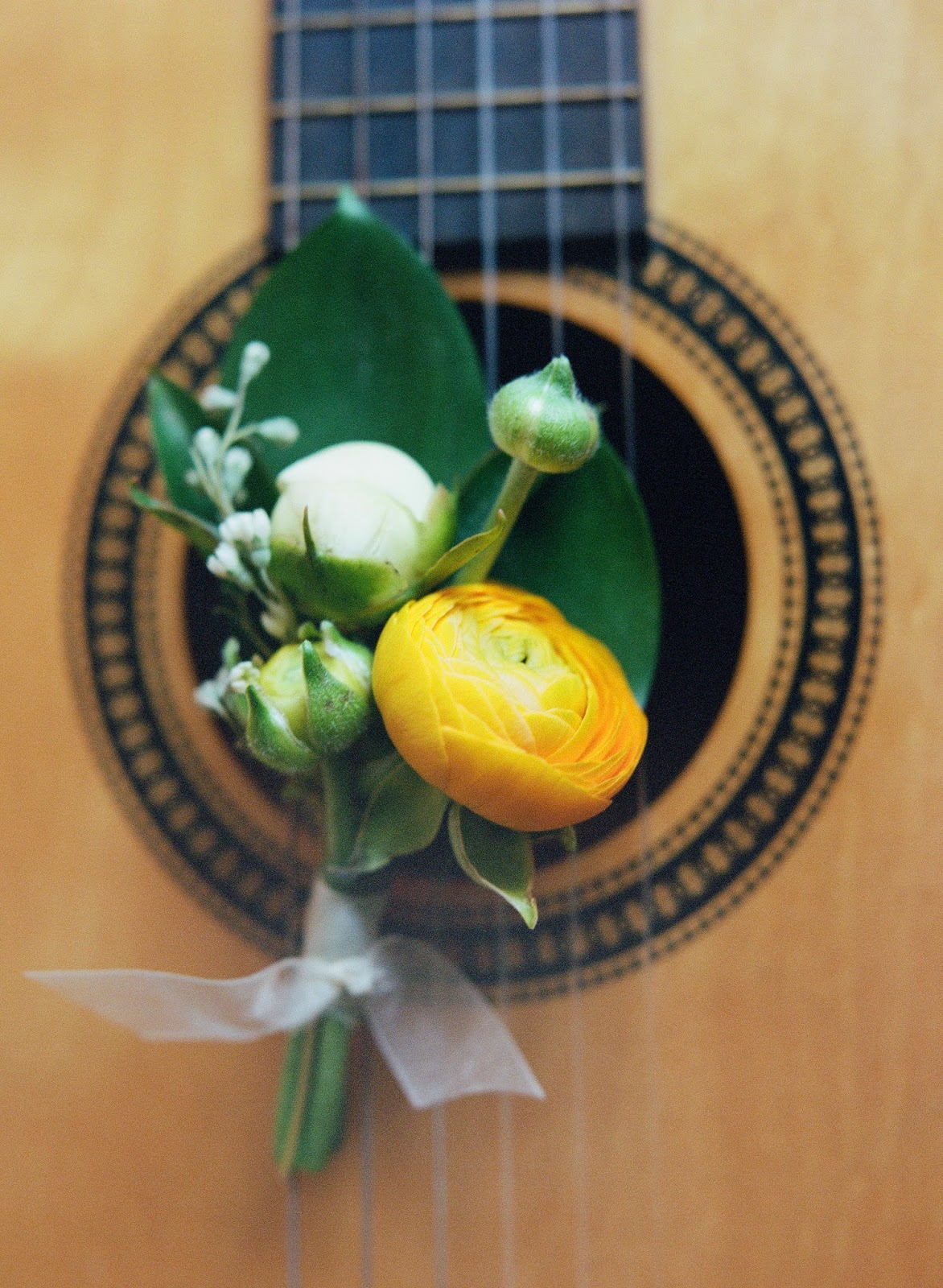 yellow ranunculus and peony spring boutonniere resting on an acoustic guitar