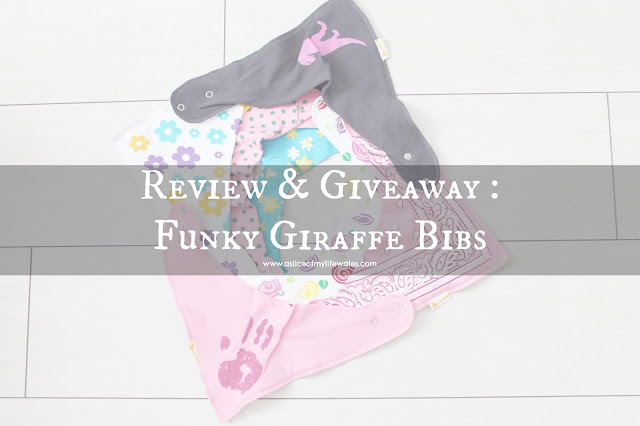 Review & Giveaway Funky Giraffe Bibs - blog header photo a selection of girls designer bibs laid out on white wooden floor