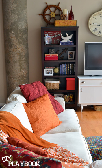 A casual television room looks great with a white couch and bright accents.