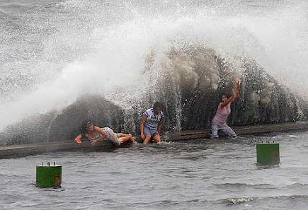 play as waves slam into the seawall at Manila\