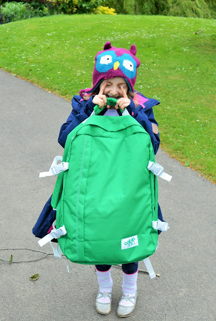 Child holdin g big green bag.