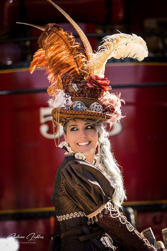Woman in steampunk clothing with big hat with feathers (corset, skirt, goggles, boots, cane)