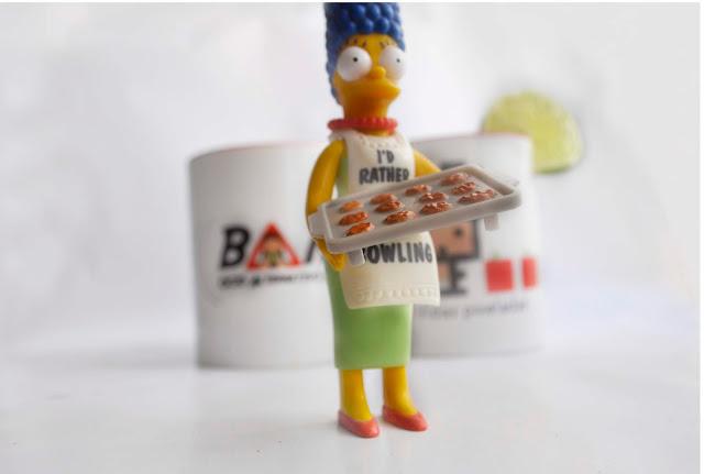 Una figura de Marge simpson con una bandeja de galletas, al fondo las tazas de Bam! y Vidas pixeladas