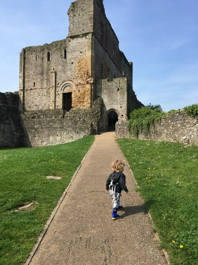 toddler on path walking towards ruins