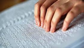 imagem de uma mão em cima de um livro de braille