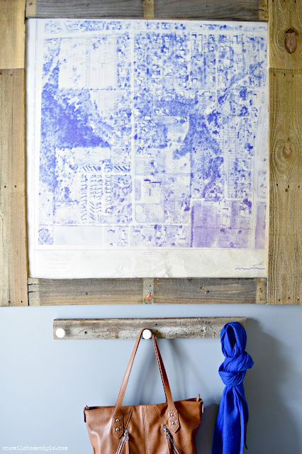 DIY a simple farmhouse entryway with a reclaimed wood organizer, and large statement art to add a personal touch to the space.