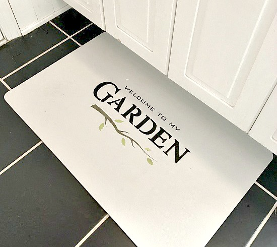 white bathroom mat with Garden stenciled on it
