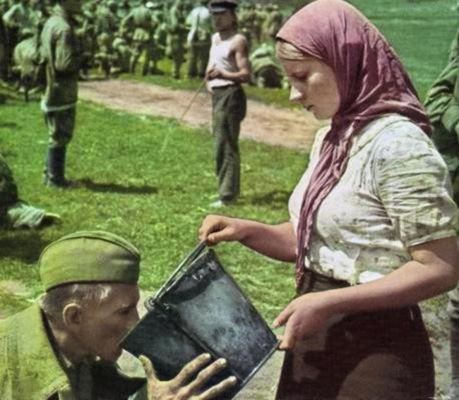 52 photos of women who changed history forever - A captured Soviet soldier is given water by a Ukrainian woman after being captured. [1941]