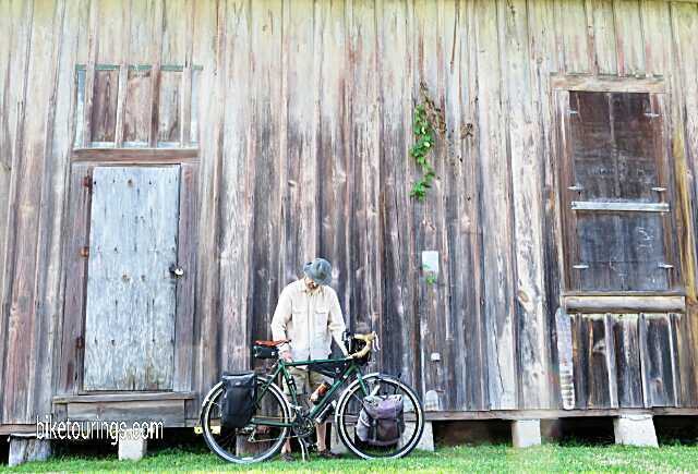 Picture of touring bike rider in front of barn