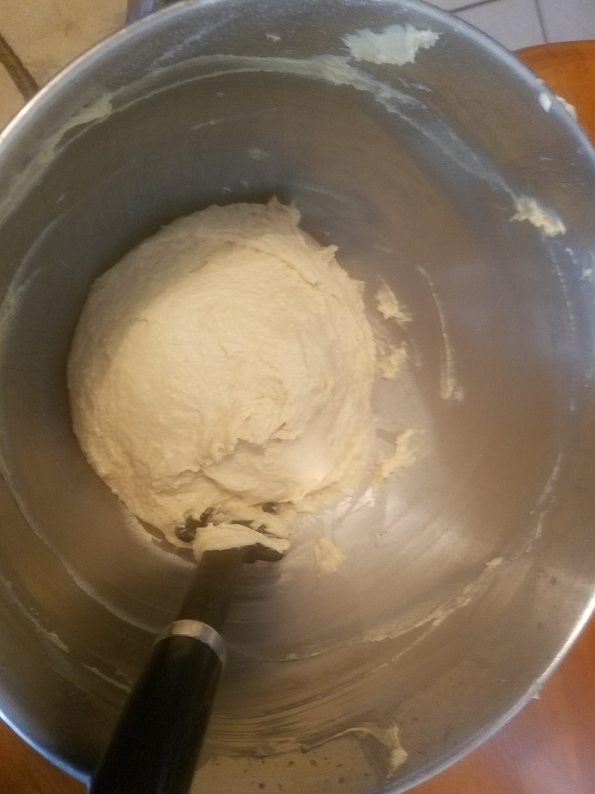 this is a bowl of dough for Pandoro Christmas Cake covered with a dish towel and pan cover to make it rise evenly