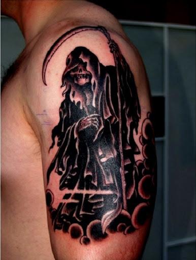Grim Reaper tatuagem de tinta preta. O reaper é visto olhando diretamente em seus deverá enquanto de pé sobre um monte de nuvens negras. O marcante preto cor faz com que o reaper ainda mais temível.