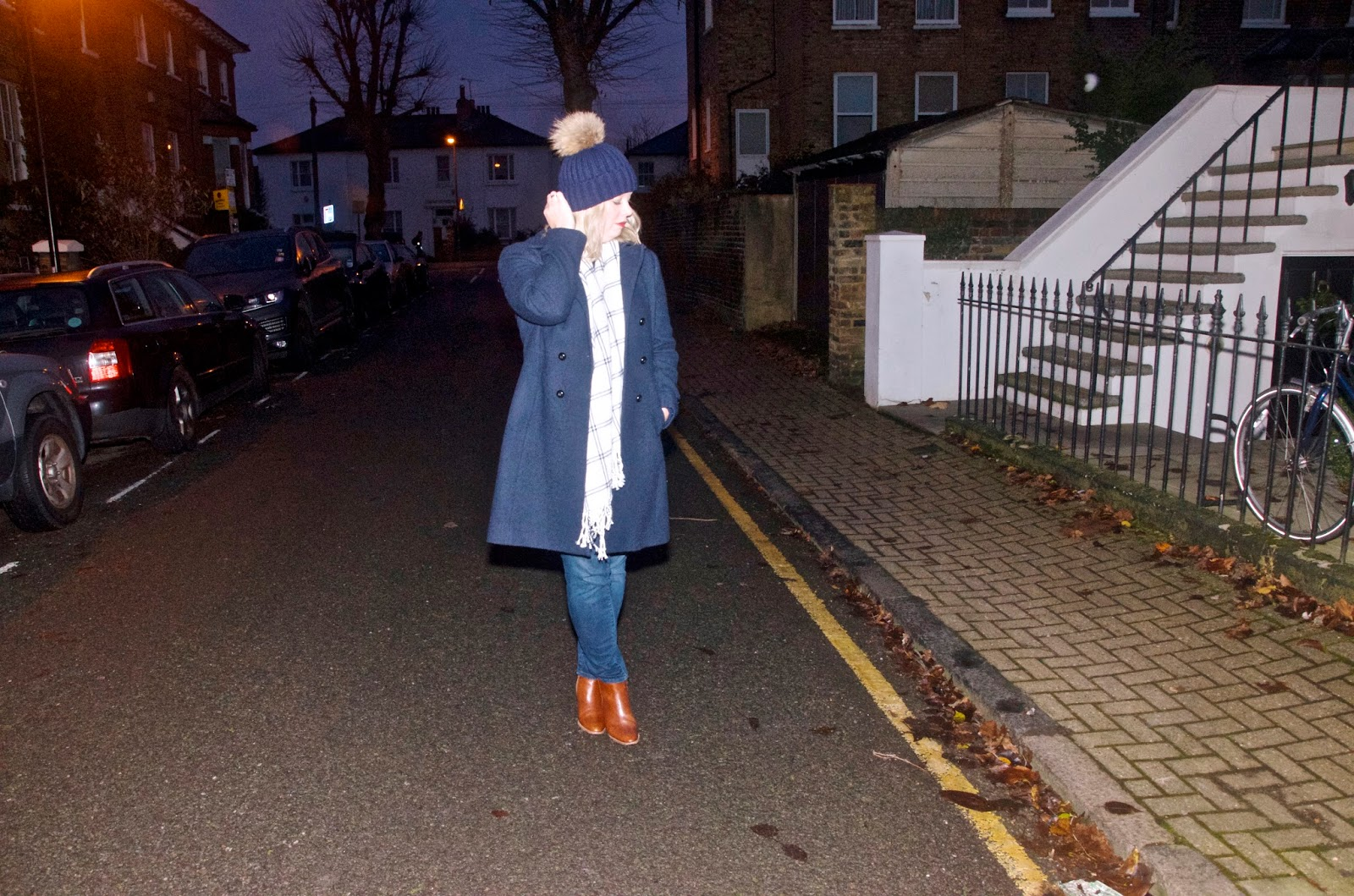 Fur beanie, white scarf, navy coat, brown boots, cobblestones and bicycle