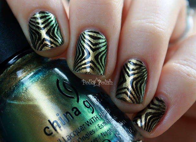 Nails manicured with China Glaze Rare and Radiant, a gold green and blue duochrome stamped with black bundle monster 221 design