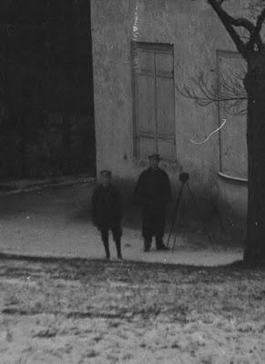 Ausschnitt - Foto von zwei Personen vor einem Haus, eine davon mit Fotoapparat auf Stativ - um 1900