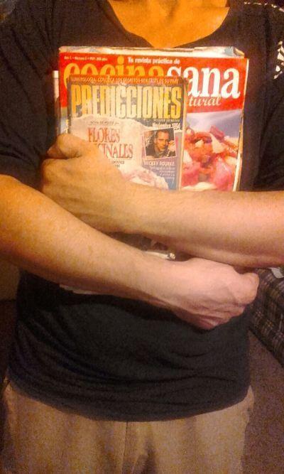 Hombre sosteniendo lote de revistas para reciclar