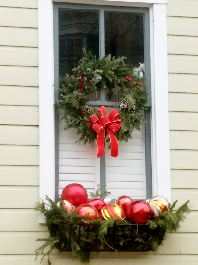 outside window decorated for christmas with wreath and window box full or colorful ornaments
