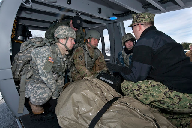 military students listening to an instructor in a helicopter
