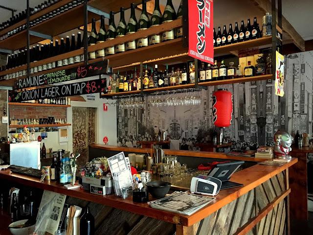 """Ở Fukuoka, nổi bật nhất, ngon không thể chê trách, có lẽ là quán mì Ichiran, những thực khách đến đây thường gọi đùa là quán mì """"Tự Kỉ"""". Vào giờ cao điểm , bữa trưa hay bữa tối, người ta vẫn thường nhẫn nại rồng rắn lặng lẽ xếp hàng nối đuôi nhau đợi được ăn mì. Bạn ngồi đối diện """"bức tường"""" gỗ,  """"o-đờ"""" mọi thứ qua một tờ giấy chi chít tỉ mẩn chu đáo các nhu cầu, tích các lựa chọn như làm bài trắc nhiệm, sau đó bạn nhét giấy vào cửa sổ nhỏ nhỏ nơi bức tường gỗ, nhân viên Tự Kỉ """"nhận lệnh"""", làm mì, rồi chuyển mì cho bạn cũng qua cửa sổ tí hi."""