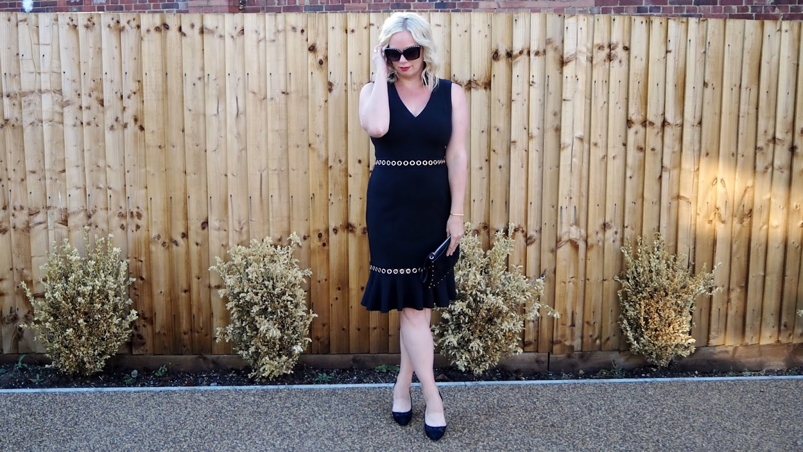 black dress with fluted hem and gold eyelet hardware