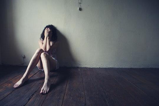 Persona depresiva sentada en el fondo de un cuarto vacio