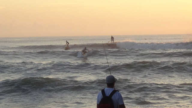 Surfing and surf fishing off Cocoa Beach, Florida