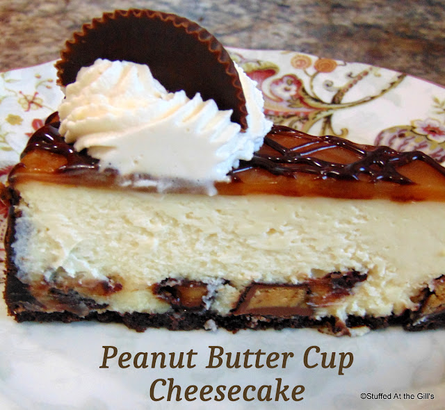 A slice of Peanut Butter Cup Cheesecake garnished with whipped cream and pieces of peanut butter cups.