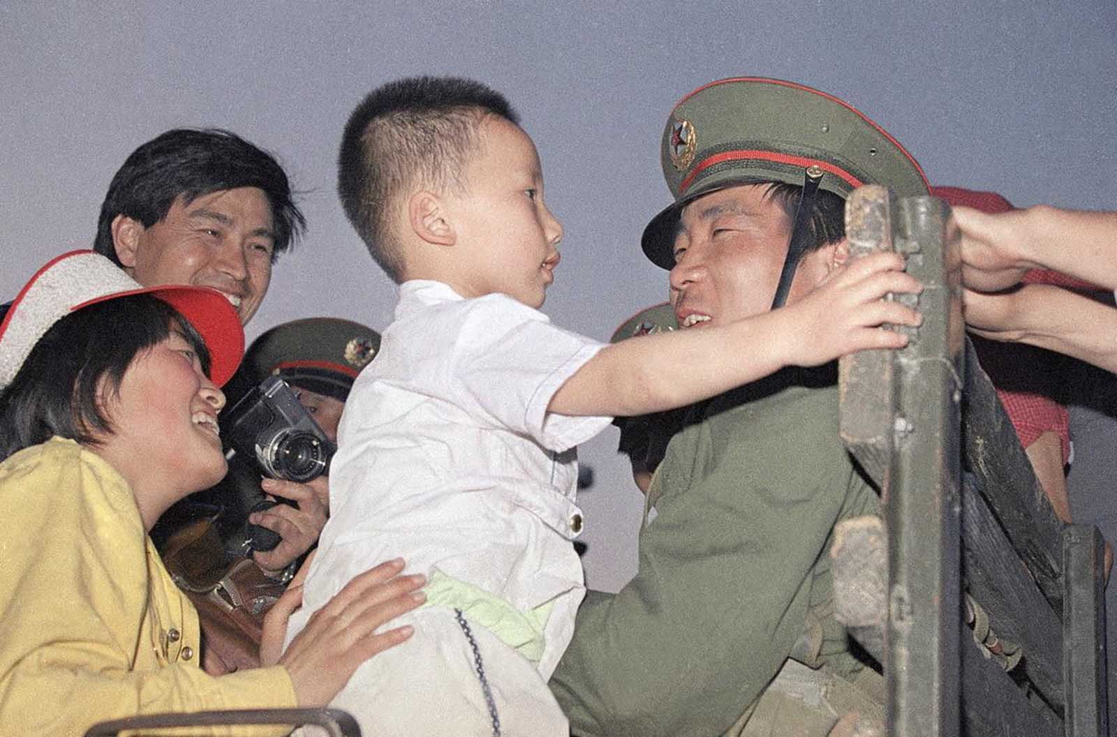 An unidentified mother introduces her son to a soldier on an army truck, 8 kilometers west of Tiananmen Square, in Beijing, on May 20, 1989. Citizens had surrounded and stopped the force.