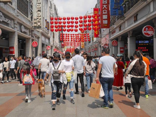people, including a few wearing face masks, at the Shangxiajiu Pedestrian Street