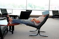 Ayaklarını masaya uzatarak ve yüzüne kitap kapatarak uyuyan tembel çalışan