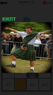 На поляне танцует мужчина в килте, национальной одежде перед зрителями