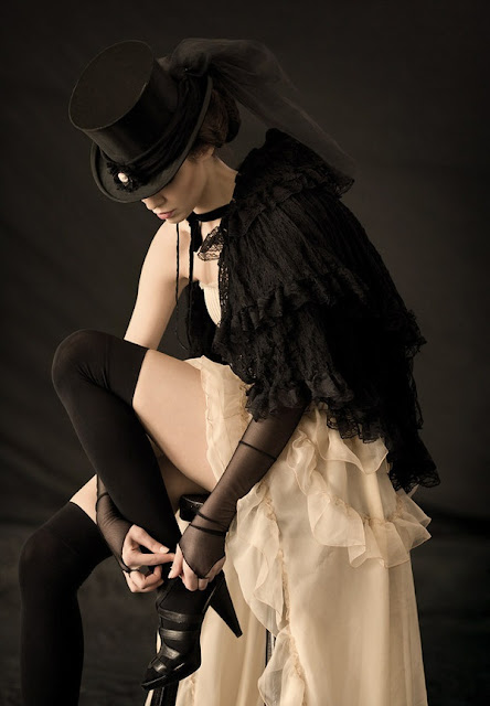 A woman wearing victorian clothing--a top hat, corset, showgirl skirt, shawl and stockings. Women's steampunk clothing with a neo-victorian emphasis. Much like victorian bride and groom or steampunk wedding attire.