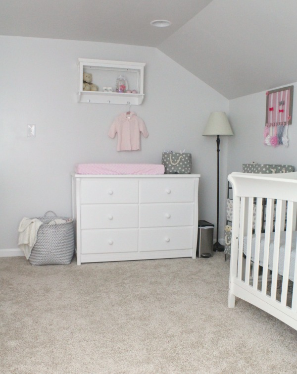 Gray white and light pink nursery for a baby girl- White dresser as a changing table and white shelf from Target