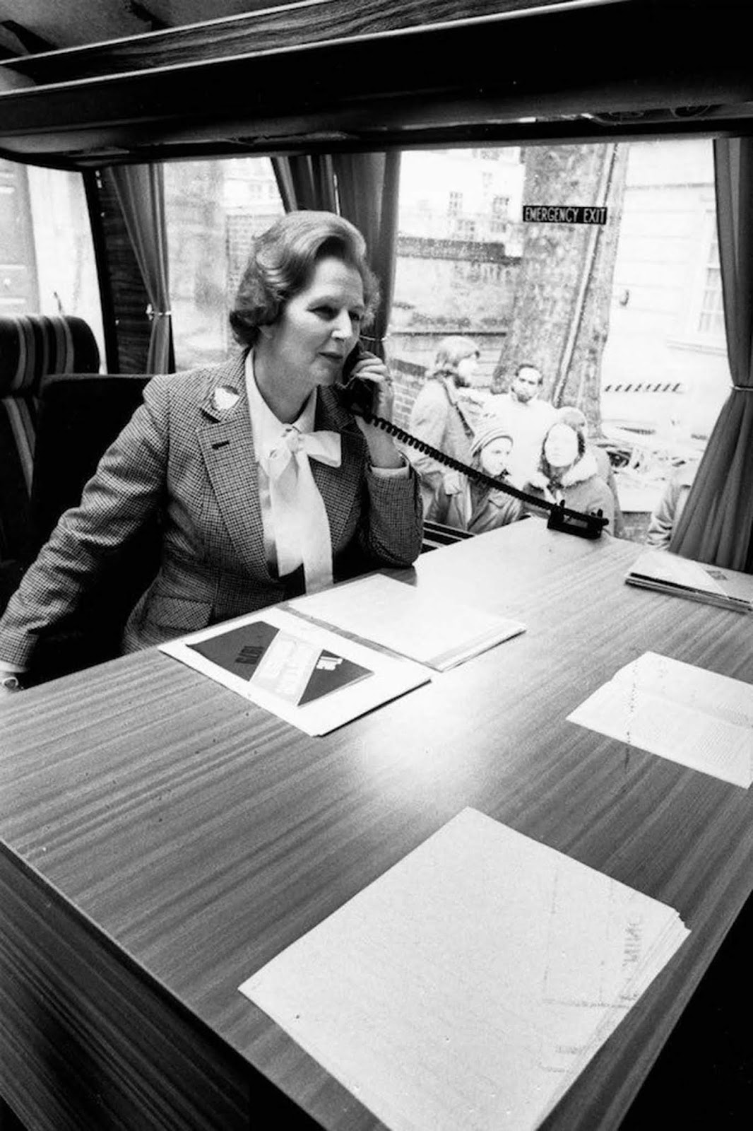 Margaret Thatcher making a telephone call in the Conservative Party coach during her election campaign. She wears a checked jacket and a blouse tied with a large bow. Her hair has a strong wave. 1979.