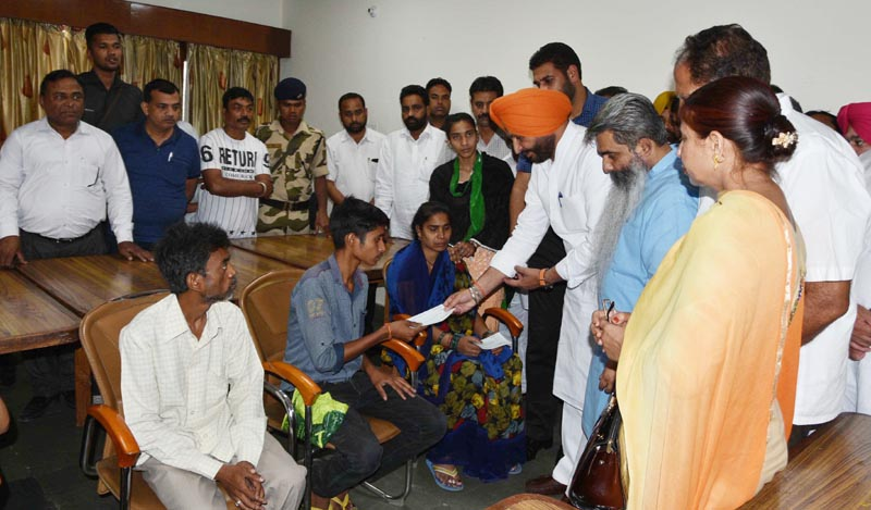 Punjab Food, Civil Supplies, and Consumer Affairs Minister Bharat Bhushan Ashu and Member of Parliament (MP) Ravneet Singh Bittu giving cheque to deceaseds' families of cylinder blast tragedy in Ludhiana