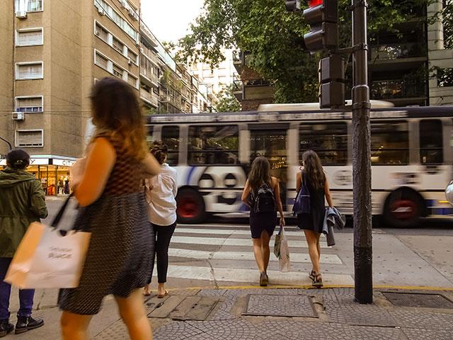 Dos jovenes comienzan a cruzar en medio del transito en CABA
